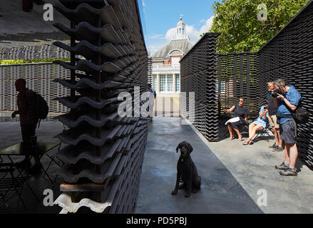 Inside pavilion looking to Serpentine Gallery with people and dog. Serpentine Summer Pavilion 2018, London, United Kingdom. Architect: Frida Escobedo, - Stock Image