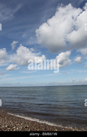 Floating clouds in a blue sky over a grey sea and a shingle shoar in Helsingor Sound, Denmark - Stock Image