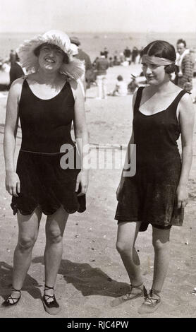 Two women on the Beach - Summer season at Deauville, Normandy, France - the rush sun hat is providing necessary protection against the heat of the rays... - Stock Image