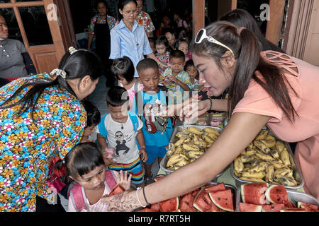 Thailand child care center for underprivileged children with helpers giving food to the children. - Stock Image