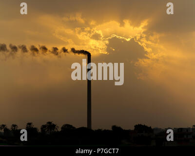 Sunset on the river Nile Egypt in an industrial area with pollution from smoking chimney increasing the dramatic orange colours in the clouds - Stock Image