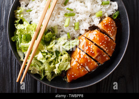 Portion of teriyaki chicken fillet with rice and lettuce close-up on a plate on the table. horizontal top view from above - Stock Image