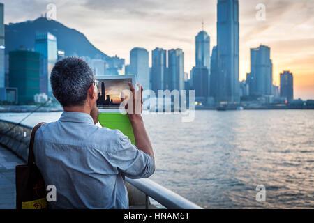 HONG KONG - OCT 9, 2013 - Man taking a photograph of Hong Kong's financial district from Wanchai Promenade at - Stock Image