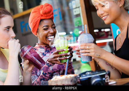 Young women friends drinking smoothies at sidewalk cafe - Stock Image
