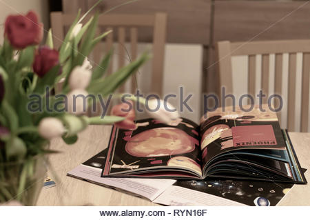 Poznan, Poland - March 8, 2019: Open book about galaxy and planets laying on a table with tulip flowers in soft focus foreground. - Stock Image