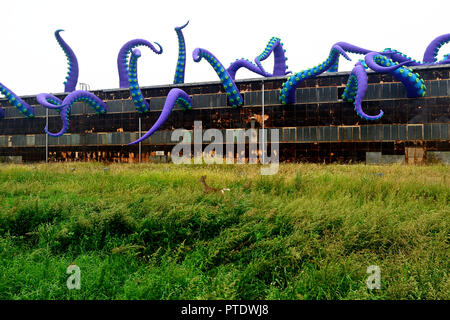 Philadelphia, USA. 8th Oct 2018. A deer runs in the field as inflatable tentacles of a temporary art installation, titled Navy Yard Sea Monster, by British artist Pedro Estrellas and Filthy Luker emerge from an old warehouse in Philadelphia, Pennsylvania, on October 8, 2018. The art work is commissioned by Philadelphia Industrial Development Corporation to promote the redevelopment of Philadelphia Navy Yard. Credit: PhotograPHL/Alamy Live News - Stock Image