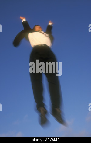 Mixed Asian Caucasian male leaping in business suit - Stock Image