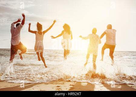 Happy family or friends at the beach running and jumping in the sunset sea. Friendship or vacations concept - Stock Image