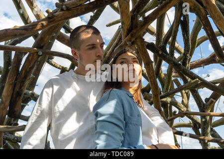 Couple of young beautiful man and woman together outdoors in sunny summer day at wooden background at countryside. - Stock Image