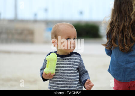 Adorable Blond Baby Boy Wearing A Sweater On The Sandy Beach, Close Up Portrait - Stock Image