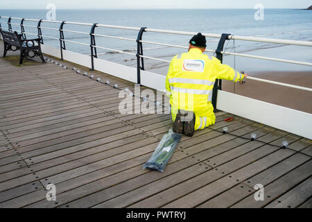 An Electrician rigging decorative strings of lights on the deck of Saltburn Pier - Stock Image