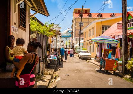 Central America, Caribbean, Lesser Antilles, Dominica, Capital Roseau, scene of daily life, street vendor and large cruise liner in background, from downtown - Stock Image