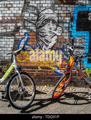 Lidl Bicycle & Mobike rental bike parked next to graffiti-covered Cemetery wall in Baruther strasse, Kreuzberg-Berlin - Stock Image