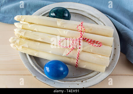 New harvest of white asparagus and colored Easter eggs, high quality raw asparagus in spring season, ingredients for Easter dinner close up - Stock Image