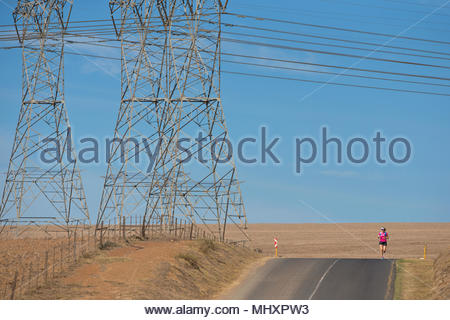 Female runner running on open road by electricity pylons in arid landscape - Stock Image