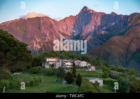 A red glow on the mountains as the sun sets above the ancient village of Fazzano in Tuscany,Northern Italy - Stock Image
