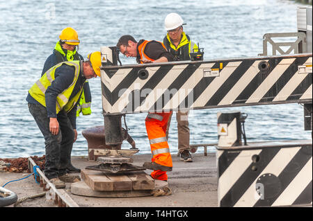 Schull, West Cork, Ireland. 16th Apr, 2019. West Cork Civil Engineering were given the task of refloating the €600,000 Schull pontoon, ready for the season.  Workers are seen preparing the crane to lift a piece of the pontoon into the water. Credit: Andy Gibson/Alamy Live News. - Stock Image