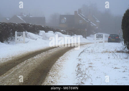 Roadside sign denoting the north Oxfordshire village of Hook Norton after snowfall and snowdrifts - Stock Image