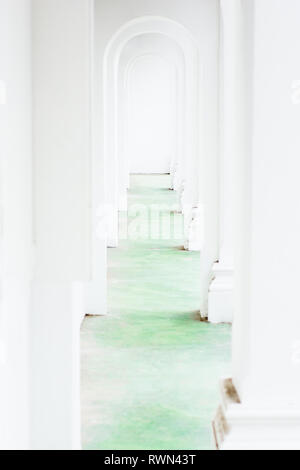 Conceptual view along bright white arched corridor tunnel with green floor. - Stock Image