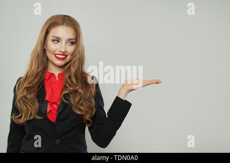 Business woman in black suit holding empty open hand on white background - Stock Image
