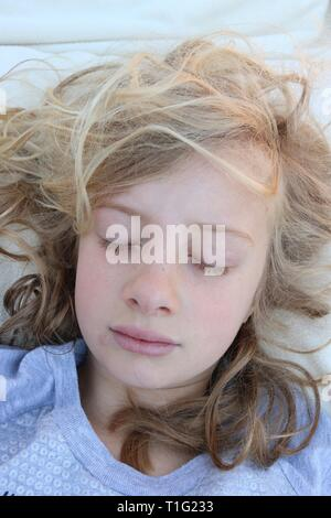 Portrait of a young blonde curly girl peacefully sleeping - Stock Image