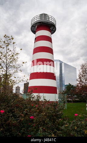 LeFrak Point lighthouse, a traditional red and white striped lighthouse on a stormy grey day, Newport Lighthouse - Stock Image