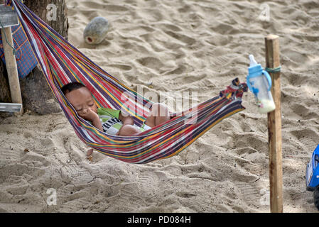 Child sleeping in a hammock on the beach at Pattaya Thailand Southeast Asia - Stock Image