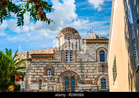An ancient Greek church in the plaka district of Athens Greece with the ancient Acropolis Hill behind as tourists enjoy the views underneath the flag - Stock Image
