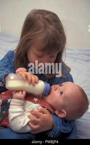 little girl bottlefeeding her baby brother - Stock Image