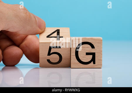 Man's Hand Changing Wooden Block From 4g To 5g On White Surface - Stock Image