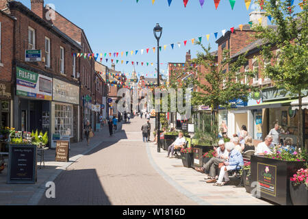 Older people sitting talking in Bridge Street, Congleton town centre, Cheshire, England, UK - Stock Image