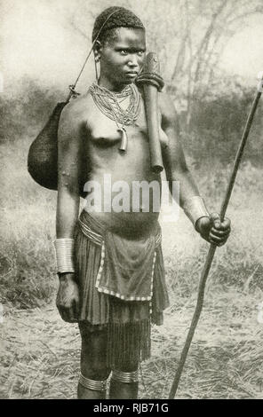 Watuta (possibly Watutsi, Watusi, Tutsi) woman, carrying a bag slung by a string across the top of her head, and an axe across her shoulder, south-east of Lake Tanganyika, East Africa (then part of the British Empire, now Tanzania). - Stock Image
