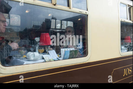 People dining on steam train in pullman carriage at Grosmont station. North York Moors Railway. North Yorkshire, England. UK - Stock Image