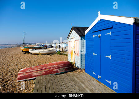 Beach huts and fishing boats on the Bulverhythe beach, West St Leonards-on-Sea, East Sussex, UK - Stock Image