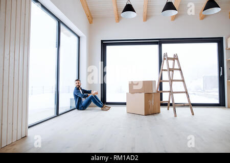 A mature man with cardboard boxes sitting on the floor, furnishing new house. - Stock Image