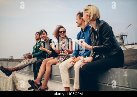 Happy young people partying on roof with drinks. Multiracial men and woman enjoying on terrace. - Stock Image