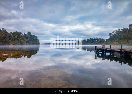 Old Jetty Lake Mapourika West Coast New Zealand, with an overcast sky reflected in the water. - Stock Image
