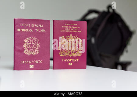 British and Italian passports standing next to each other, with backpack out of focus in the background. - Stock Image