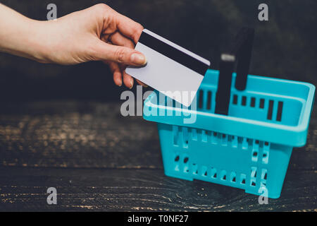add to cart concept: hand holding payment card with shopping basket next to it - Stock Image