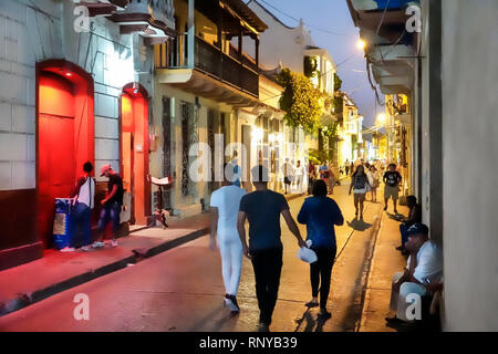 Cartagena Colombia Old Walled City Center centre Getsemani night nightlife Hispanic resident residents man walking strolling pedestrians - Stock Image