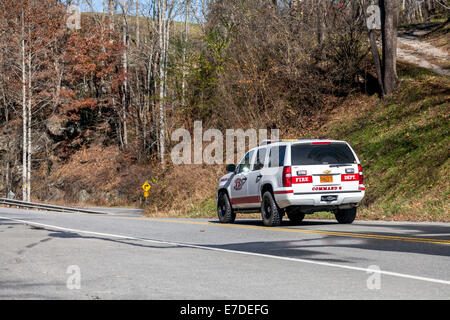 Emergency fire vehicle traveling on NC 107 along west fork Tuckasegee River just south of Tuckasegee Lake, North - Stock Image