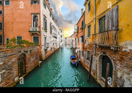 A small boat docks in the emerald green water of a colorful canal in a residential area, as the sun sets under storm clouds in Venice, Italy. - Stock Image