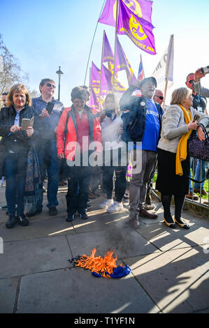 London, UK. 29th Mar, 2019. Pro Brexit campaigners burn an EU flag outside the Houses of Parliament in London today as they show their anger at not leaving the EU today causing traffic chaos in the city . MP's are sitting today to debate leaving the European Parliament on the day it was originally supposed to happen Credit: Simon Dack/Alamy Live News - Stock Image