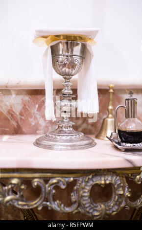 Catholic liturgical objects displayed over marble table at church. Chalice, wine pitcher and bell - Stock Image