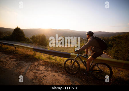 Side view of male athlete with bicycle by guard rail against clear sky - Stock Image
