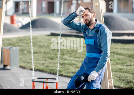 Portrait of a tired workman in uniform on the playground outdoors - Stock Image