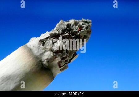 One burning cigarette macro shot on isolated background - Stock Image