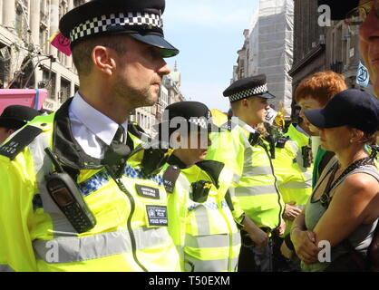 London, UK. 19th Apr, 2019. Police and protesters seen facing off during the demonstration.Environmental activists from Extinction Rebellion movement occupy London's Oxford Circus for a 5th day. Activists parked a pink boat in the middle of the busy Oxford Circus road junction blocking the streets and causing traffic chaos. Credit: Keith Mayhew/SOPA Images/ZUMA Wire/Alamy Live News - Stock Image