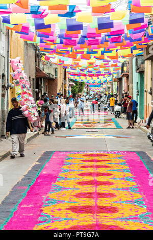 A giant tapestry like floral carpet made from colored sawdust and decorated with flowers during the 8th Night Celebration marking the end of the Feast of St Michael in the central Mexican town of Uriangato, Guanajuato. Every year the town decorates 5km of road with religious icons in preparation for the statue of the patron saint to be paraded through the town. Uriangato became an international sensation after wowing Brussels with their floral carpet displayed at the Brussels Grand-Place during the Belgium Floral Carpet festival. - Stock Image