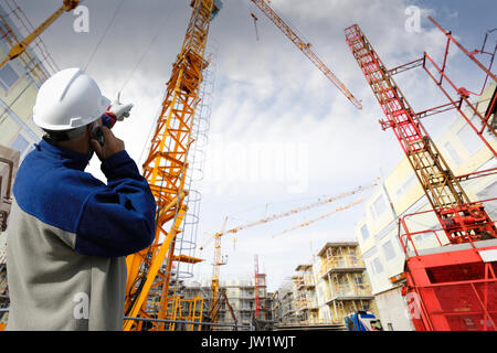 construction worker directing large mobile crane - Stock Image